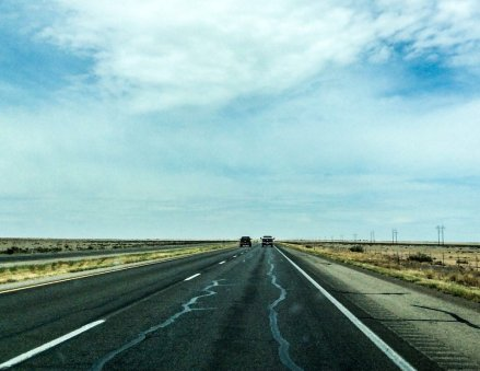 Straight road, trucks and big sky. Highway 285 New Mexico April 6, 2018